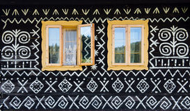 Décorations peintes sur le mur de la cabane en rondins dans Cicmany, Slovaquie Photographie stock libre de droits