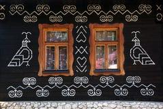 Décorations peintes sur le mur de la cabane en rondins dans Cicmany, Slovaquie Photos stock