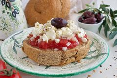 DDakos traditional Greek appetizer on a traditional plate with ceramic olive oil jar, dry rye bread, olives and olive branch. Heal Stock Photos