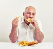 Ddle-verouderde mens die hamburger eten royalty-vrije stock fotografie