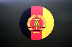 DDR - Flagge und Mantel-vonarme stockbild