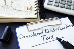 DDT do imposto da distribuição de dividendo escrito na folha de papel fotos de stock