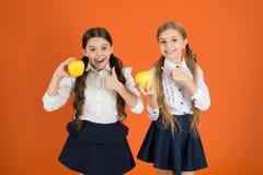 De är smakliga Frukter är höga i vitamin Gulliga skolflickor som äpplen Skolbarn med det sunda äpplemellanmålet royaltyfria bilder