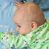 De één éénjarigebaby kruipt krachtig aan zijn doel Weinig vrolijke jongen in een lichtgroen kostuum met schapen stock afbeelding