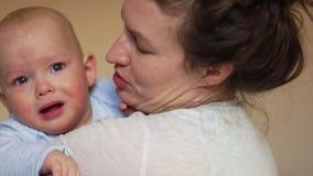 De één éénjarigebaby schreeuwt in de wapens van zijn moeder Dicht portret, de dag van de moeder stock footage