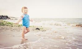 De één éénjarigejongen speelt op het strand stock afbeelding