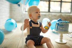 De één éénjarigejongen viert zijn eerste verjaardag en eet feestelijke cake stock foto's