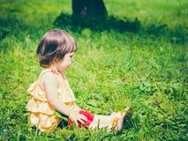 De éénjarige zitting van het babymeisje op gras en weg het kijken Royalty-vrije Stock Foto's
