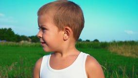 de 4 éénjarigenjongen in een witte t-shirt glimlacht schuchter in de camera, dan kijkt weg Portret van een leuk kind met klein stock footage
