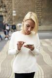 ¡De Ð que daña charla de la muchacha del inconformista en el smartphone que se coloca en el ambiente urbano Imagen de archivo libre de regalías