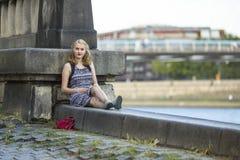 ¡De Ð que daña la muchacha que se sienta en una 'promenade' de piedra Imagen de archivo