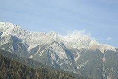 De österrikiska fjällängarna täckas med snö och skogar Arkivfoton