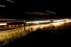 De övergående ljusen av bilar och lastbilar på natten Royaltyfria Bilder