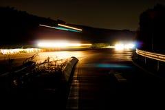 De övergående ljusen av bilar och lastbilar på natten Arkivfoto
