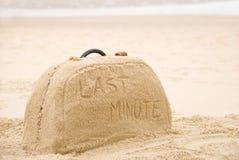 Maleta hecha fuera de la arena con la escritura fotografía de archivo