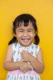 关闭亚洲孩子暴牙的微笑的面部面孔的面孔激动在黄色墙壁用途的幸福儿童可爱的情感和de的 库存图片
