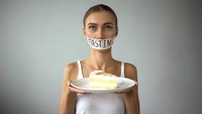 De aan anorexie lijdende die pastei van de meisjesholding, het vasten woord op vastgebonden mond, verbod op snoepjes wordt geschr royalty-vrije stock foto's