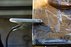 De aan de grond zettende klem met de kabel van de lassenmachine wordt bevestigd aan de metaallijst aangaande de productie royalty-vrije stock afbeelding