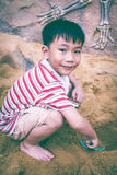 De aanbiddelijke Aziatische jongen heeft pret het graven in het zand op een de zomerdag Stock Afbeeldingen