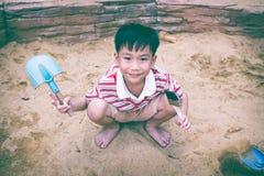 De aanbiddelijke Aziatische jongen heeft pret het graven in het zand op een de zomerdag Stock Fotografie