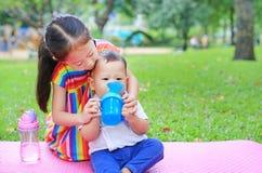 De aanbiddelijke Aziatische zusterzitting op roze matrasmat neemt geeft haar weinig broer aan drinkwater van Baby sippy kop met s royalty-vrije stock foto