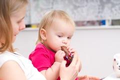 De aanbiddelijke baby eet chocolade met moeder Stock Afbeelding