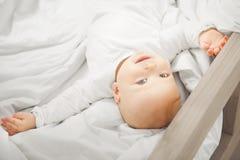 De aanbiddelijke baby ligt op terug met gelukkig gezicht stock foto