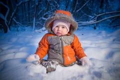 De aanbiddelijke baby zit in diepe sneeuw Stock Foto