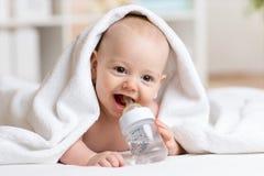 De aanbiddelijke babyjongen drinkt water van verpakte fles Royalty-vrije Stock Foto's