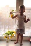 De aanbiddelijke jongen verkiest de eerste de lentebloem om aan mamma te geven Stock Foto's
