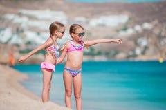 De aanbiddelijke meisjes genieten van de vakantie van het de zomerstrand Stock Afbeelding
