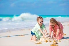 De aanbiddelijke meisjes hebben samen pret op wit strand royalty-vrije stock foto