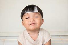 De aanbiddelijke mollige jongen met mollig cheeked en sluit smilingly ogen Vooraanzicht van jong geitje met ziekte Stock Afbeelding