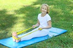 De aanbiddelijke school verouderde jong geitjemeisje het spelen sporten met een elastiekje en een mat in openlucht in het park Ge Royalty-vrije Stock Foto
