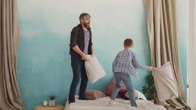 De aanbiddelijke speelse jongen bestrijdt hoofdkussens, lacht en heeft pret met zijn houdende van vader Vrolijke mensen, gelukkig stock videobeelden