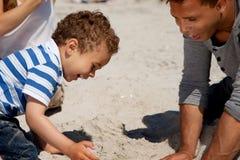De aanbiddelijke Spelen van de Jongen in het Zand met Zijn Papa Royalty-vrije Stock Afbeeldingen