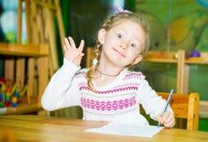 De aanbiddelijke tekening van het kindmeisje met kleurrijke potloden in kinderdagverblijfruimte Jong geitje in kleuterschool in d Stock Afbeeldingen