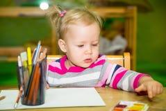 De aanbiddelijke tekening van het kindmeisje met kleurrijke potloden in kinderdagverblijfruimte Jong geitje in kleuterschool in d Royalty-vrije Stock Foto's