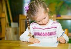 De aanbiddelijke tekening van het kindmeisje met kleurrijke potloden in kinderdagverblijfruimte Jong geitje in kleuterschool in d Stock Afbeelding