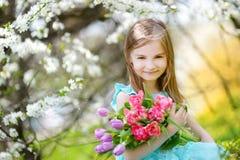 De aanbiddelijke tulpen van de meisjeholding voor haar moeder in kersentuin Stock Fotografie