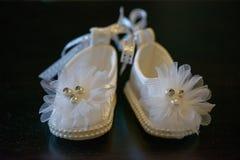De aanbiddelijke witte schoenen van het babymeisje met pareldetails en sparkly decoratie royalty-vrije stock afbeeldingen