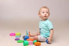 De aanbiddelijke zitting van de babyjongen op de vloer en het spelen met zijn speelgoed Stock Foto's