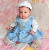 De aanbiddelijke zitting van het babymeisje met glimlach Stock Afbeelding