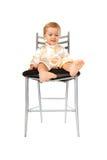 De aanbiddelijke zitting van het babymeisje op een stoel stock afbeeldingen