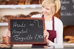 De Aanbieding van serveersterholding slate with op het bij Bakkerij wordt geschreven die Stock Foto's