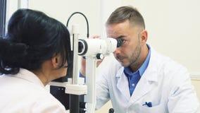 De aandachtige oftalmoloog onderzoekt de ogen van zijn patiënt royalty-vrije stock fotografie