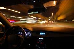 De aandrijving van de nacht met auto in motie stock foto