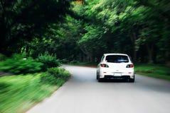 De aandrijving van de snelheid na witte auto Royalty-vrije Stock Foto