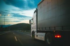 De aandrijving van de vrachtwagenauto op weg in avond De lading van het vrachtwagenvervoer Vervoer en verzending Snelheid en leve royalty-vrije stock foto's