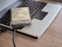 De aandrijving wordt verbonden met een notitieboekjecomputer op een houten bureau Met het concept het houden van informatie in de stock fotografie